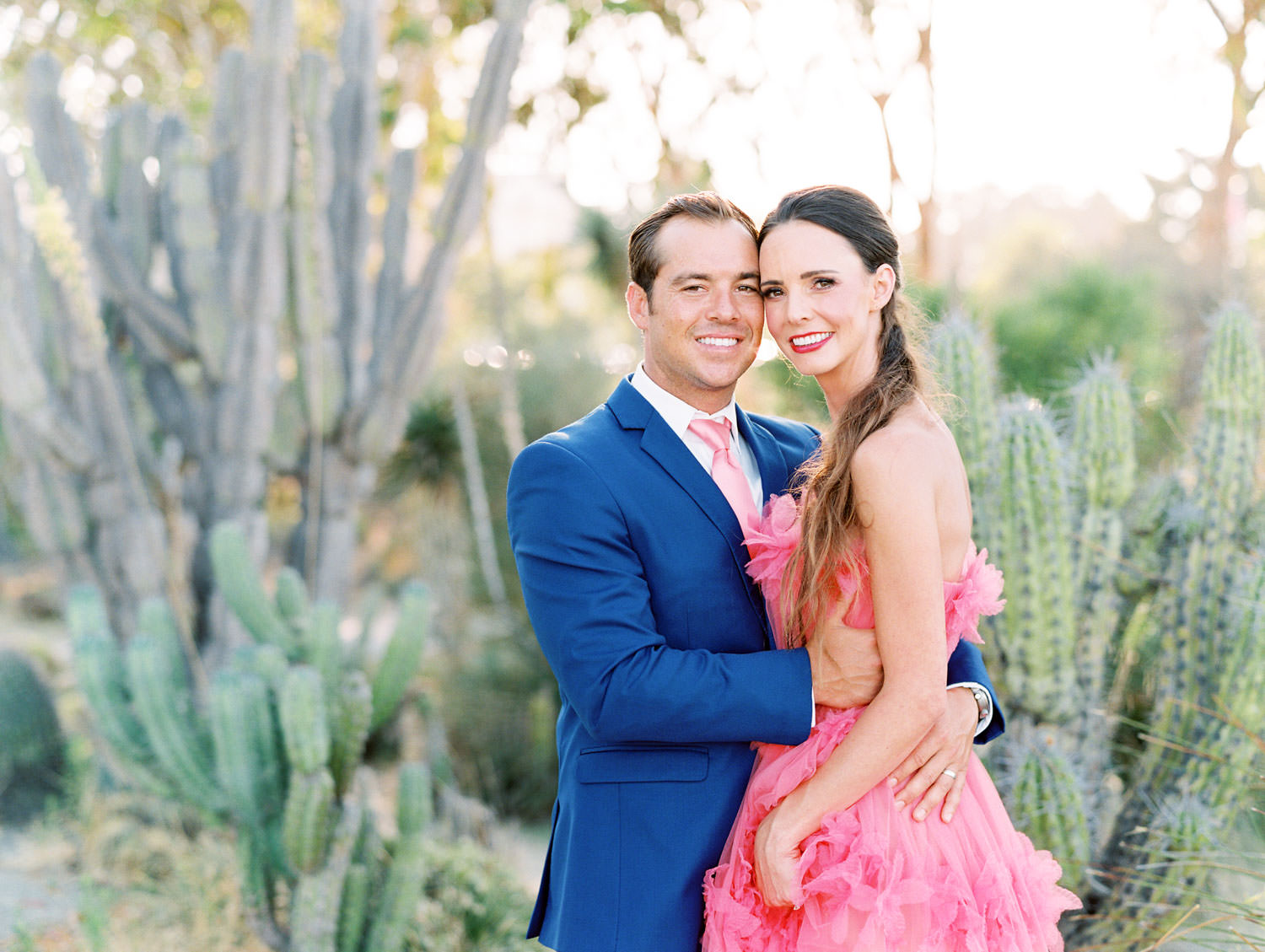 Bride in pink strapless Marchesa Notte gown holding bouquet in a cactus garden. Groom in blue suit and pink tie to match his wife. Balboa Park San Diego Anniversary Photos by Cavin Elizabeth Photography