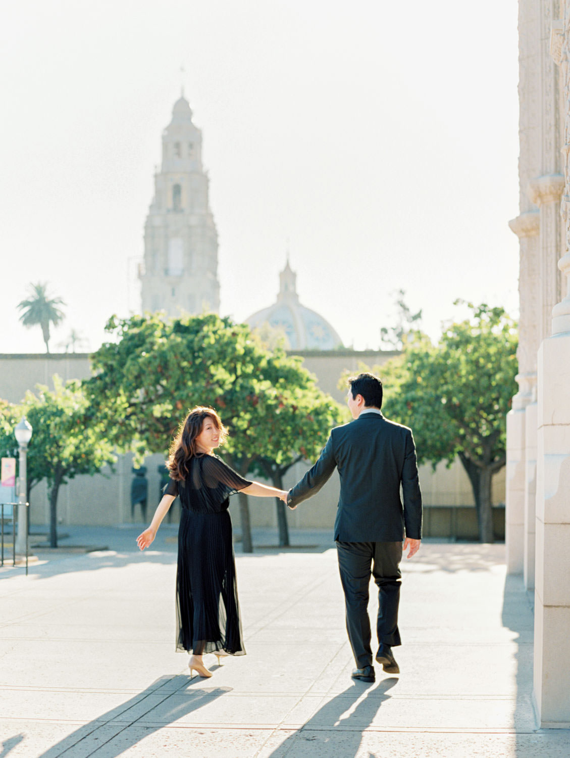 Engagement photos at Balboa Park with bride in black dress and groom in dark grey suit, film photographer Cavin Elizabeth in San Diego