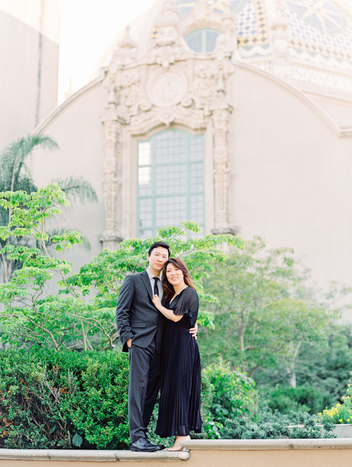 Engagement photos at Balboa Park bell tower with bride in black dress and groom in dark grey suit, film photographer Cavin Elizabeth in San Diego