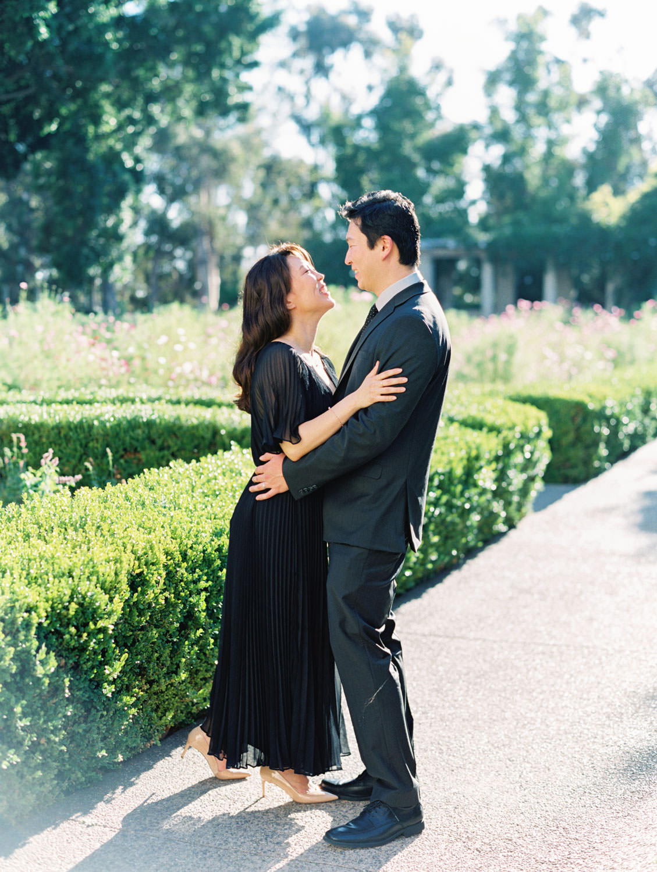 Engagement photos at Balboa Park garden with bride in black dress and groom in dark grey suit, film photographer Cavin Elizabeth in San Diego