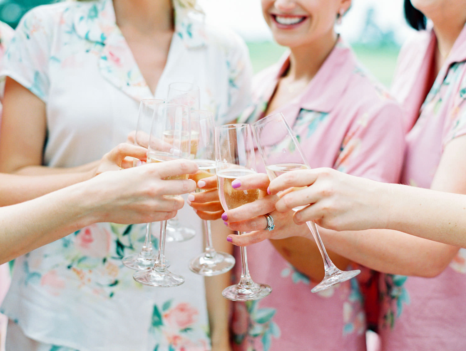 Bride in white silk pajamas with floral pattern and bridesmaids in pink matching silk pjs toasting with champagne, Lodge at Torrey Pines wedding, film photography by Cavin Elizabeth Photography