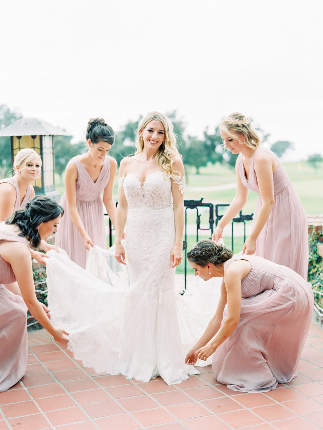 Bridesmaids in lavender dresses helping bride into off shoulder Pronovias lace wedding gown, Lodge at Torrey Pines wedding, film photography by Cavin Elizabeth Photography