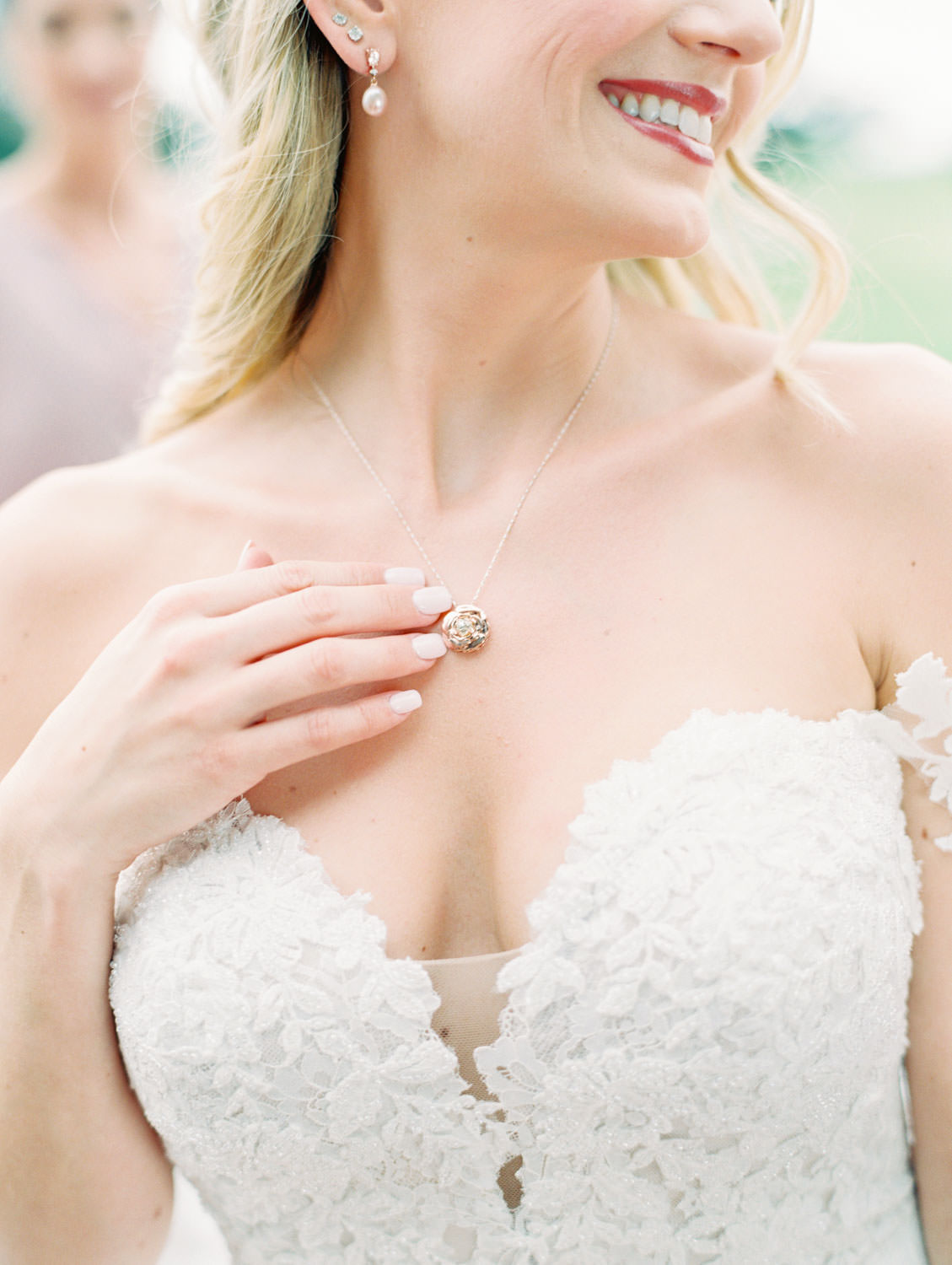 Bride touching family necklace in off shoulder Pronovias lace wedding gown, Lodge at Torrey Pines wedding, film photography by Cavin Elizabeth Photography