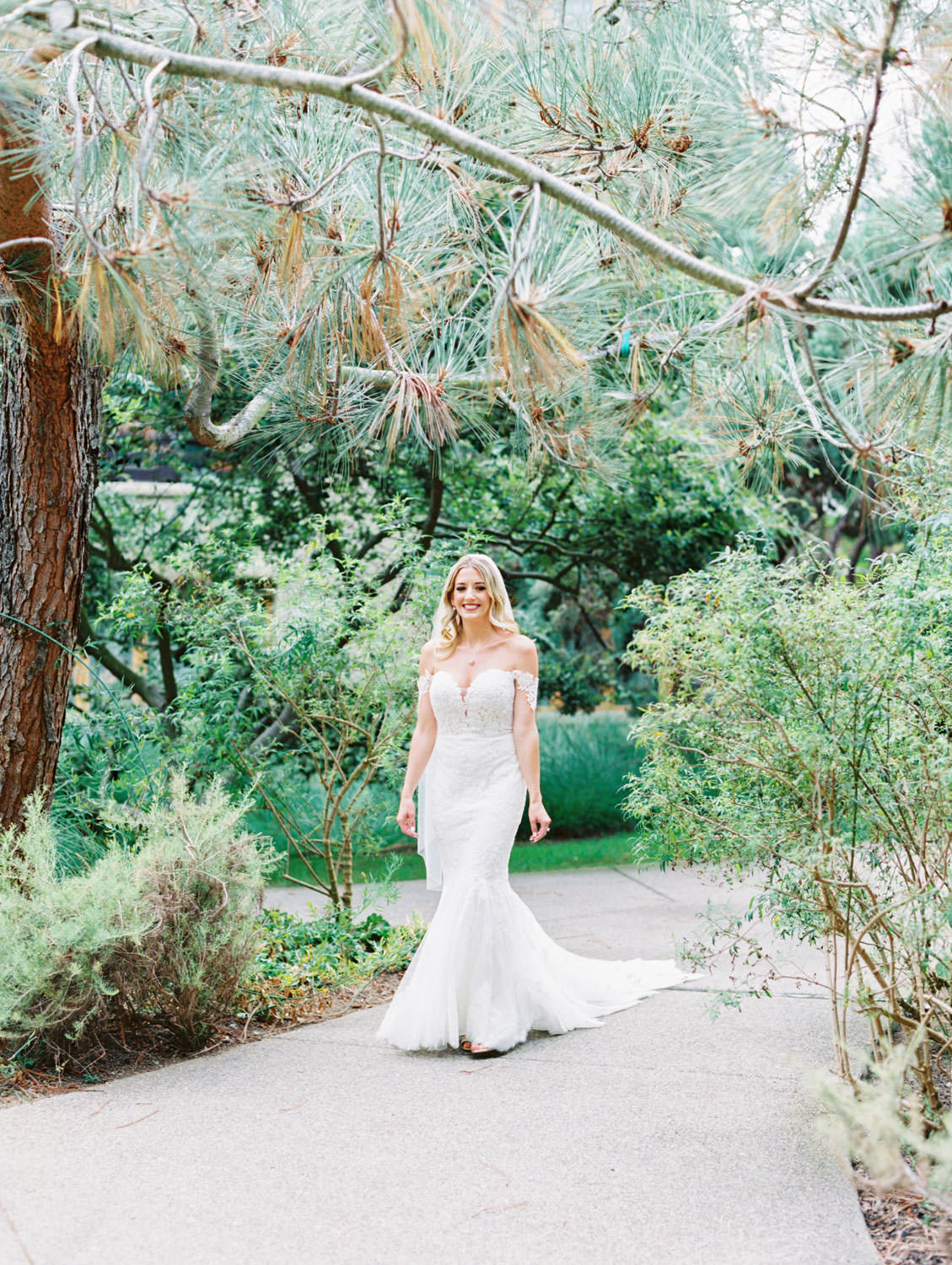 Bride in Pronovias off shoulder lace gown walking toward groom for first look, Lodge at Torrey Pines wedding, film photography by Cavin Elizabeth Photography