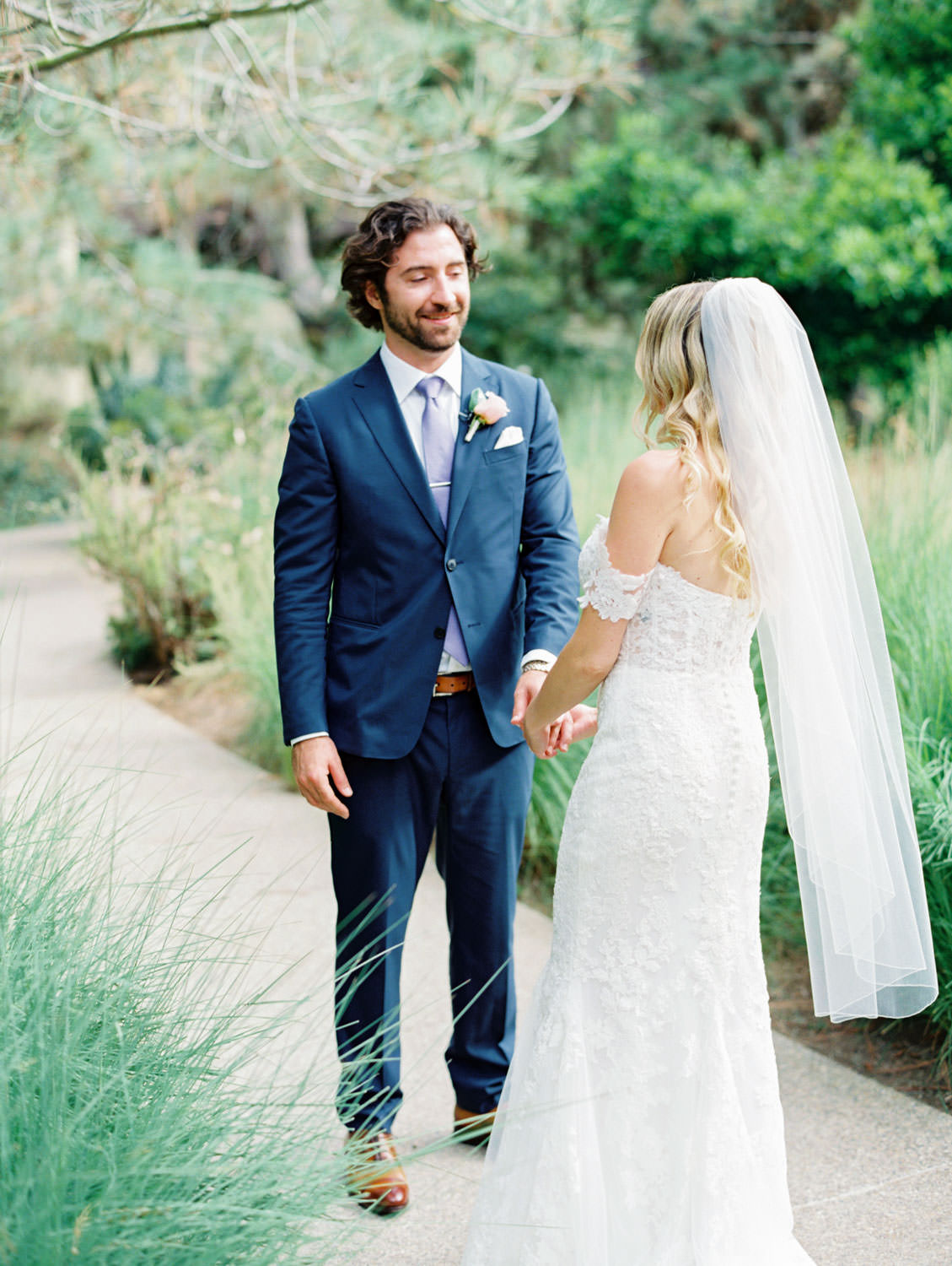 Bride in Pronovias off shoulder lace gown walking toward groom for first look and his reaction, Lodge at Torrey Pines wedding, film photography by Cavin Elizabeth Photography