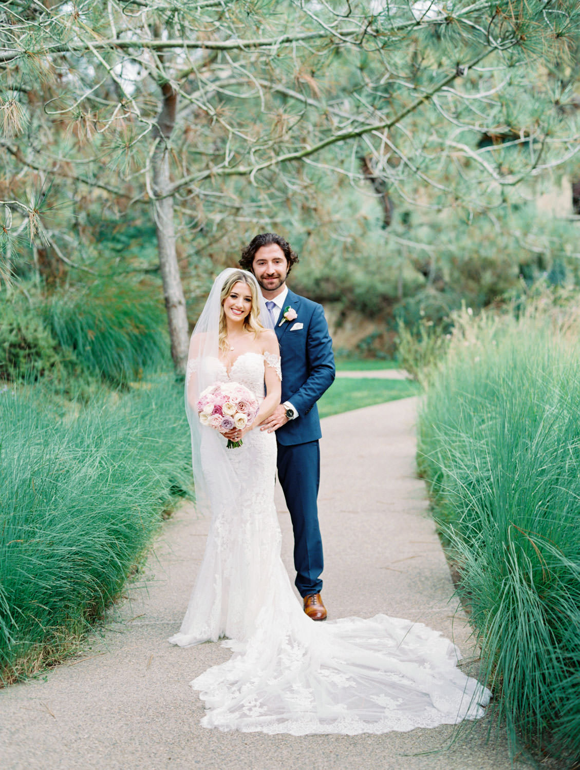 Bride in Pronovias off shoulder lace gown and long train posing with groom in navy suit and rose boutonniere, Lodge at Torrey Pines wedding, film photography by Cavin Elizabeth Photography