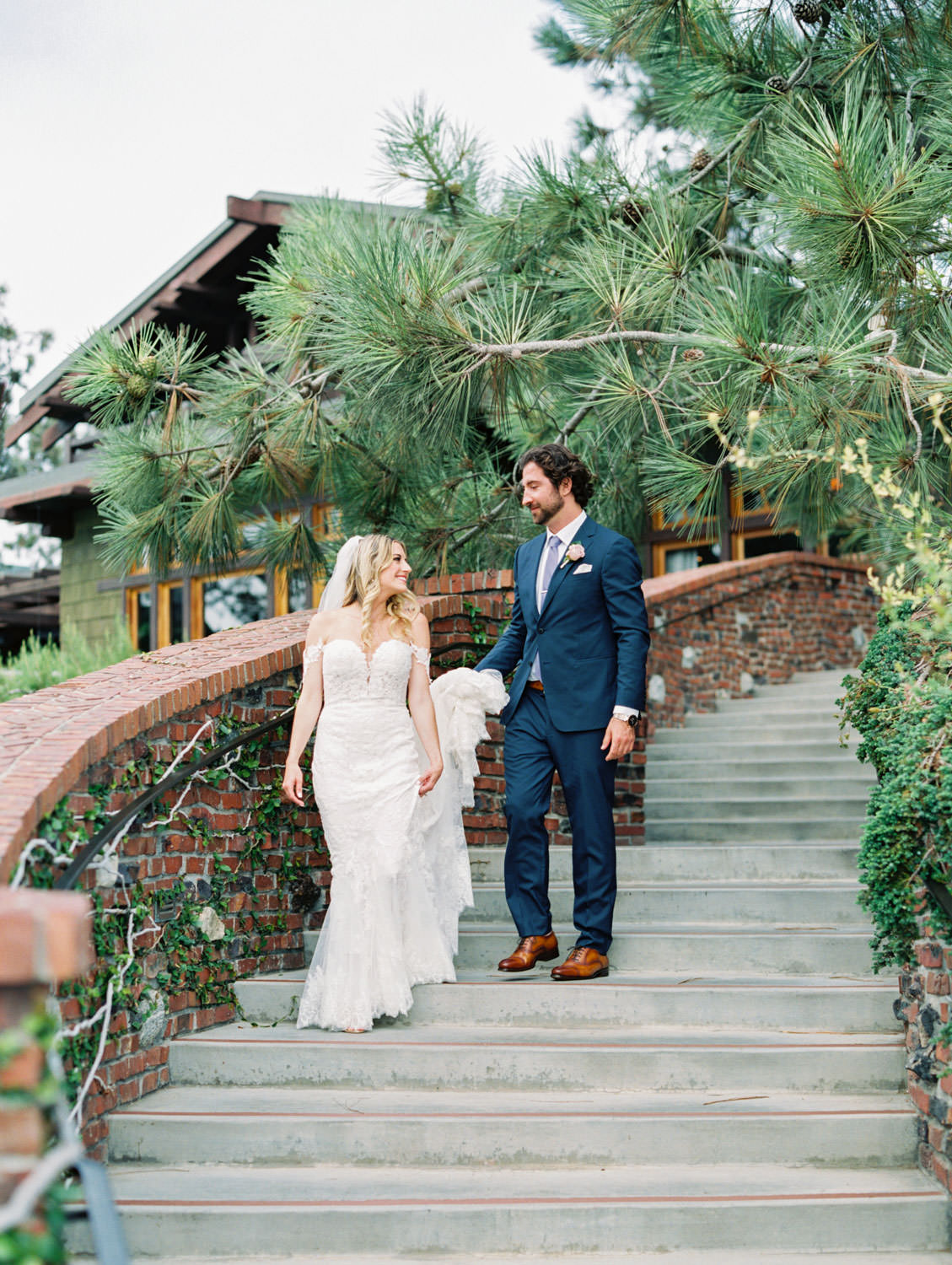 Bride in Pronovias off shoulder lace gown and long train and veil walking down stairs with groom in navy suit and rose boutonniere, Lodge at Torrey Pines wedding, film photography by Cavin Elizabeth Photography