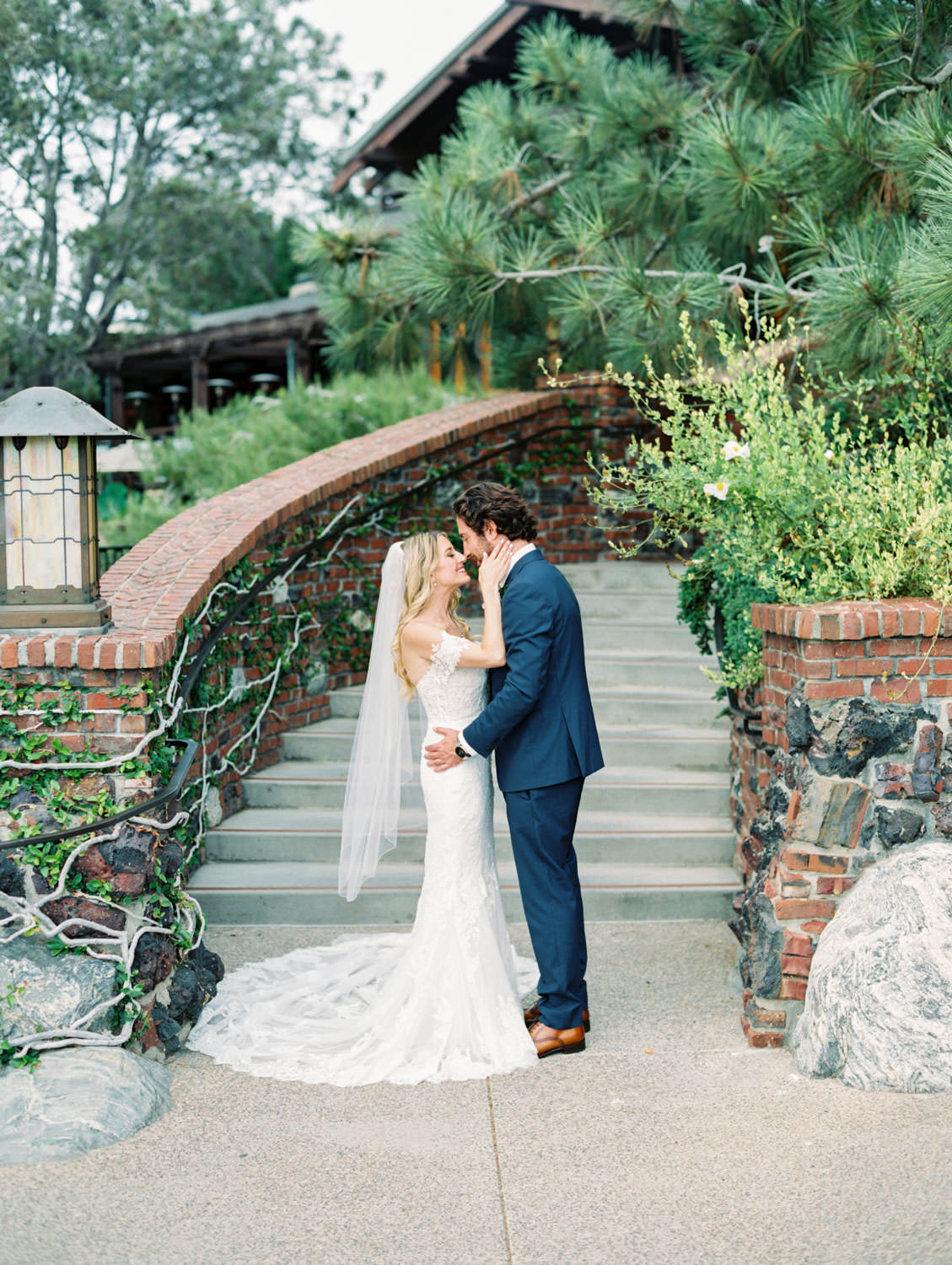 Bride in Pronovias off shoulder lace gown and long train and veil kissing groom in navy suit and rose boutonniere, Lodge at Torrey Pines wedding, film photography by Cavin Elizabeth Photography