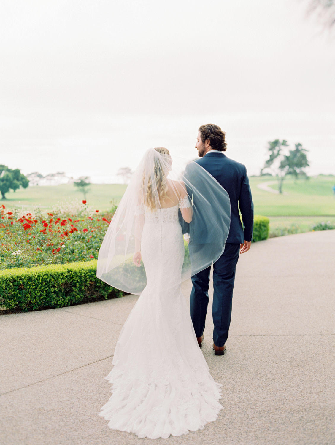 Bride in Pronovias off shoulder lace gown and long train and veil walking on garden pathway with groom in navy suit and rose boutonniere, Lodge at Torrey Pines wedding, film photography by Cavin Elizabeth Photography