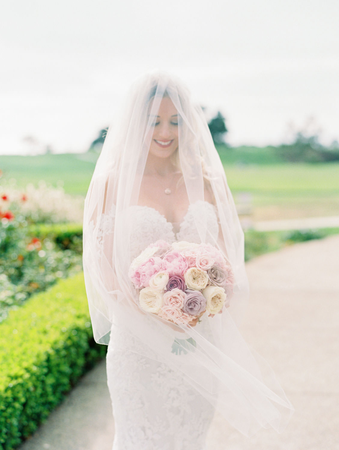 Bride in Pronovias off shoulder lace gown and long train and veil holding a bouquet with blush, lavender, and ivory roses, fine art bridal portrait, Lodge at Torrey Pines wedding, film photography by Cavin Elizabeth Photography