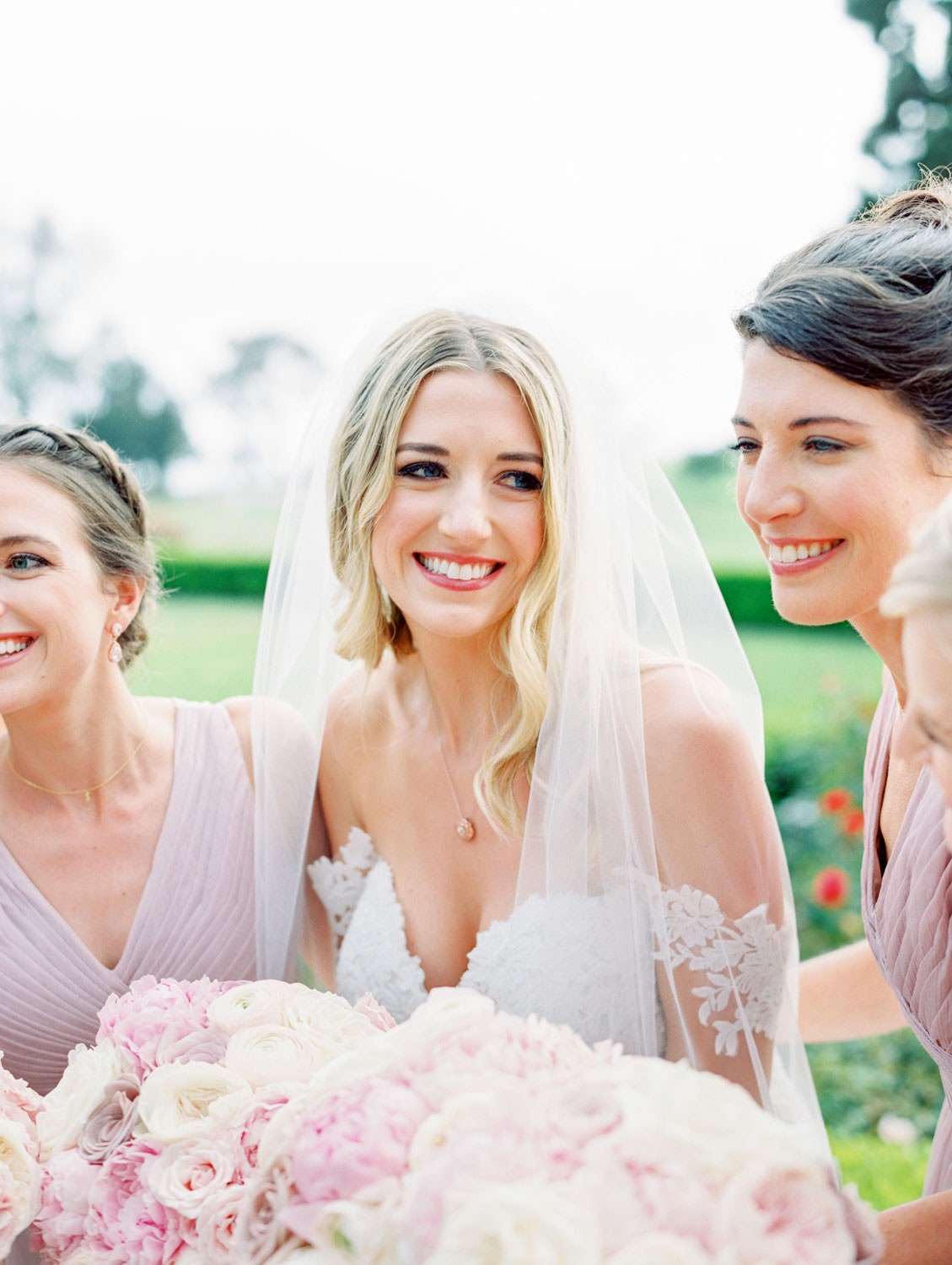 Bride in Pronovias off shoulder lace gown and long train and veil holding a bouquet with blush, lavender, and ivory roses, bridesmaids in lavender dresses, Lodge at Torrey Pines wedding, film photography by Cavin Elizabeth Photography
