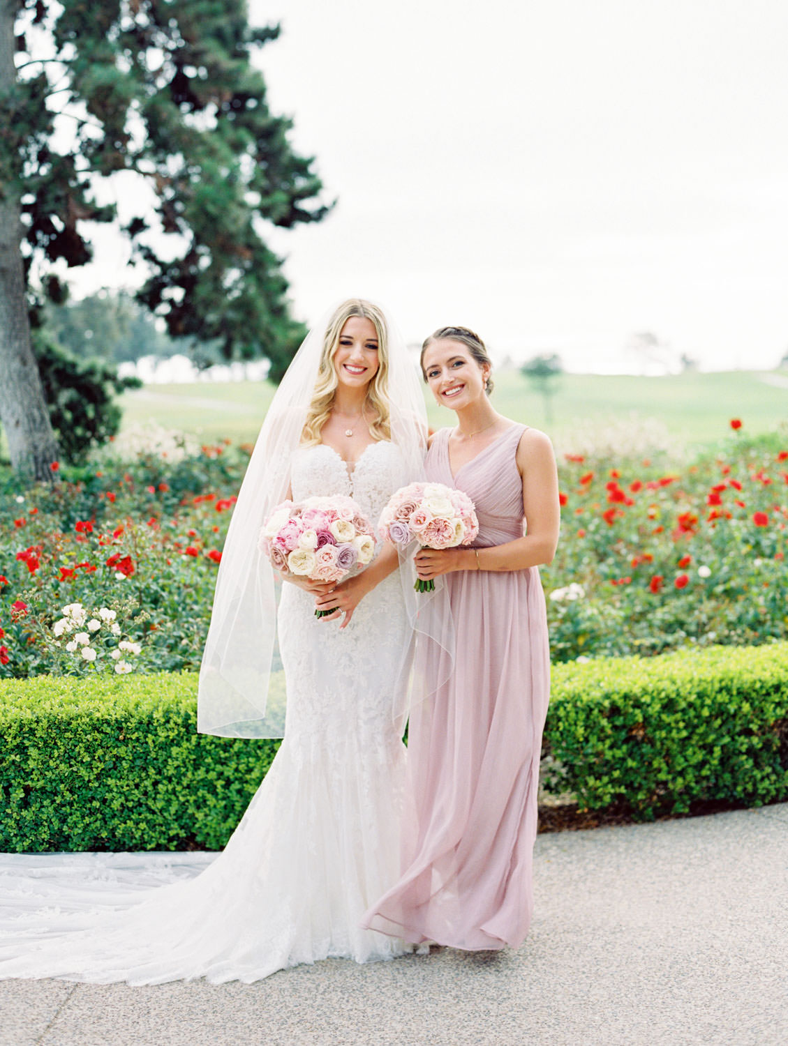 Bride in Pronovias off shoulder lace gown and long train and veil holding a bouquet with blush, lavender, and ivory roses, maid of honor in lavender dresses, Lodge at Torrey Pines wedding, film photography by Cavin Elizabeth Photography