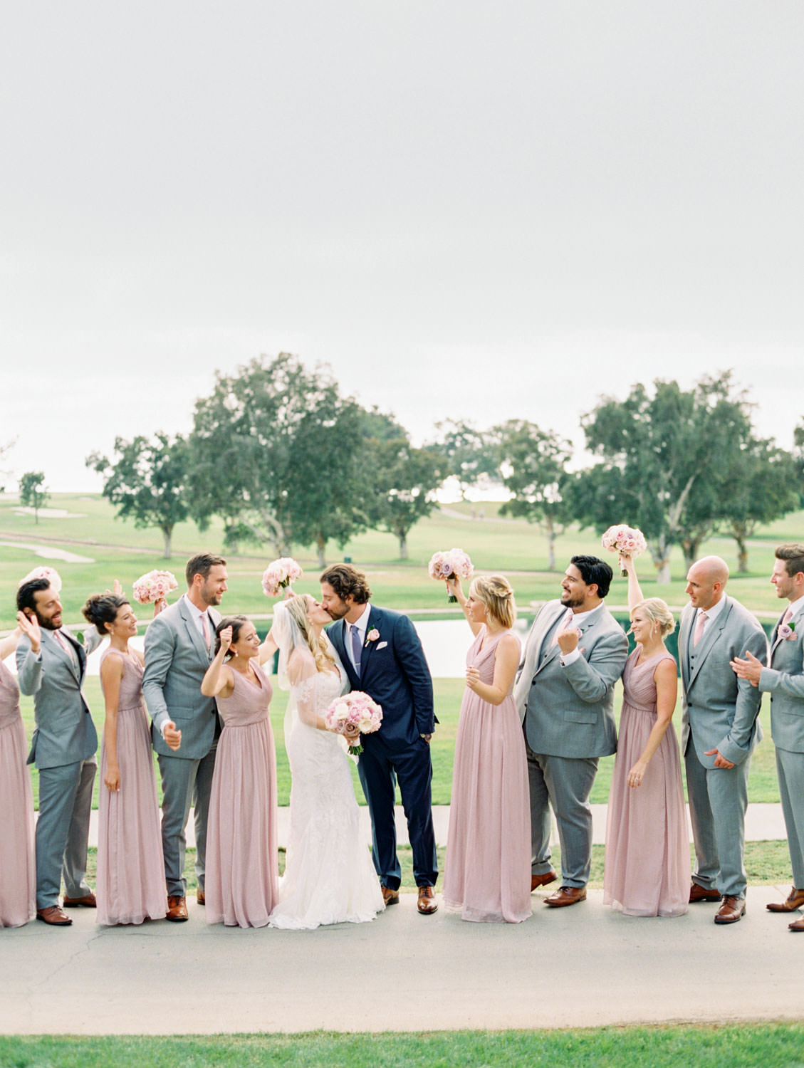 Bride in Pronovias off shoulder lace gown and long train and veil holding a bouquet with blush, lavender, and ivory roses, bridesmaids in lavender dresses and groomsmen in light grey suits and groom in navy suit, Lodge at Torrey Pines wedding, photography by Cavin Elizabeth Photography