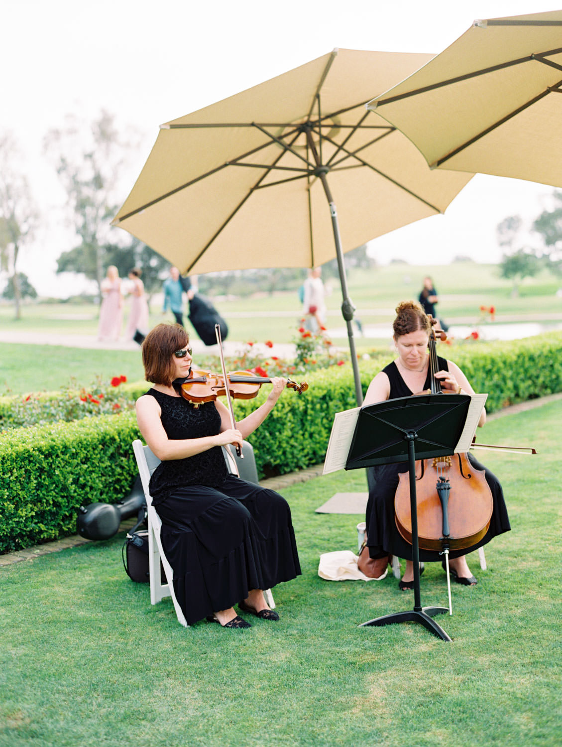 Musicians during cocktail hour outside at a rustic upscale venue in San Diego, Lodge at Torrey Pines wedding, film photography by Cavin Elizabeth Photography