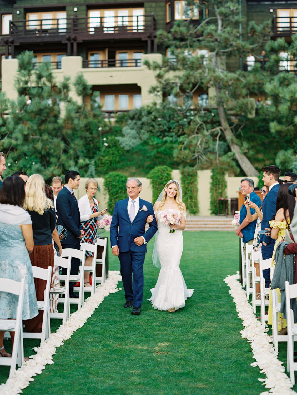 Bride walking down the grassy aisle with petals on either side at a rustic upscale venue in San Diego, Lodge at Torrey Pines wedding, film photography by Cavin Elizabeth Photography