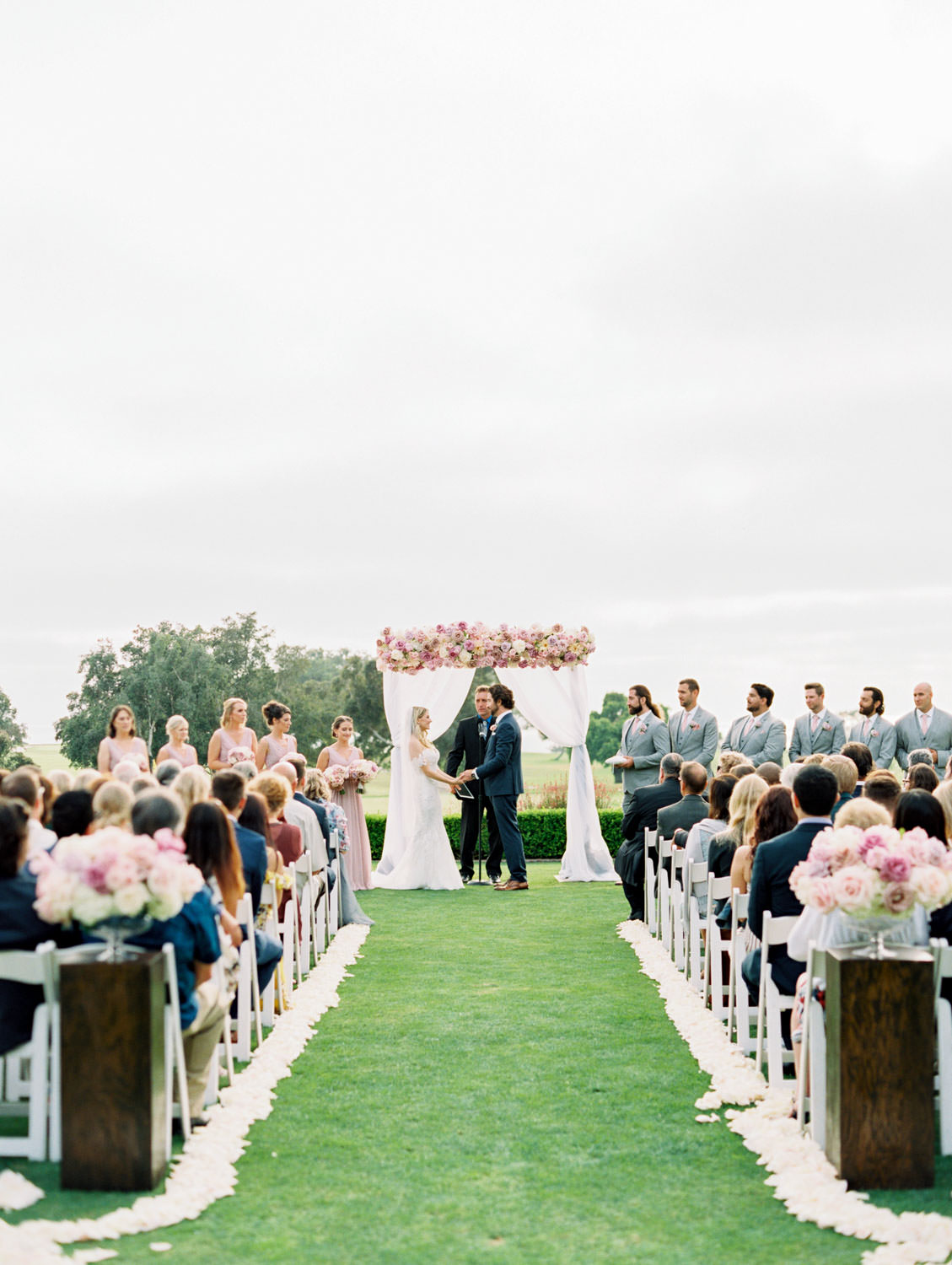 Couple reading vows during ceremony, Ceremony on grassy lawn with white chairs, aisle arrangements with ivory, pink, and lavender arrangements, ceremony white draping with large arrangement of roses on top of the arch, Lodge at Torrey Pines wedding, film photography by Cavin Elizabeth Photography
