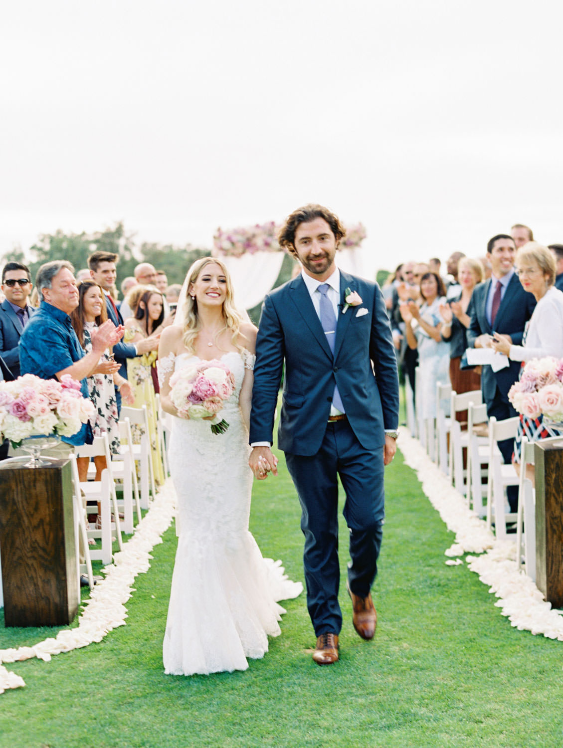 Couple walking down the aisle after the ceremony, Ceremony on grassy lawn with white chairs, aisle arrangements with ivory, pink, and lavender arrangements, ceremony white draping with large arrangement of roses on top of the arch, Lodge at Torrey Pines wedding, film photography by Cavin Elizabeth Photography