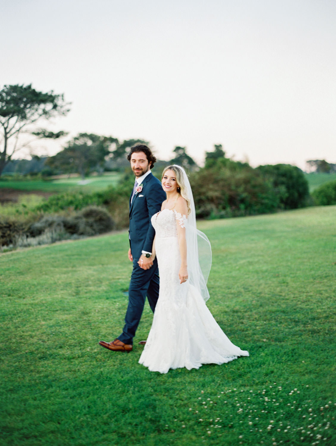 Bride in Pronovias off shoulder lace gown and long train and veil walking on grassy hill with groom in navy suit and rose boutonniere, Lodge at Torrey Pines wedding, film photography by Cavin Elizabeth Photography
