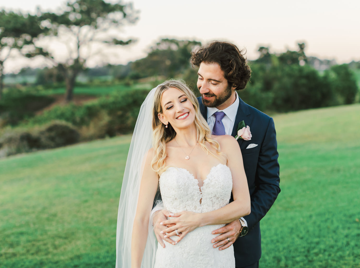 Bride in Pronovias off shoulder lace gown and long train and veil on grassy hill with ocean views with groom in navy suit and rose boutonniere, Lodge at Torrey Pines wedding, photography by Cavin Elizabeth Photography