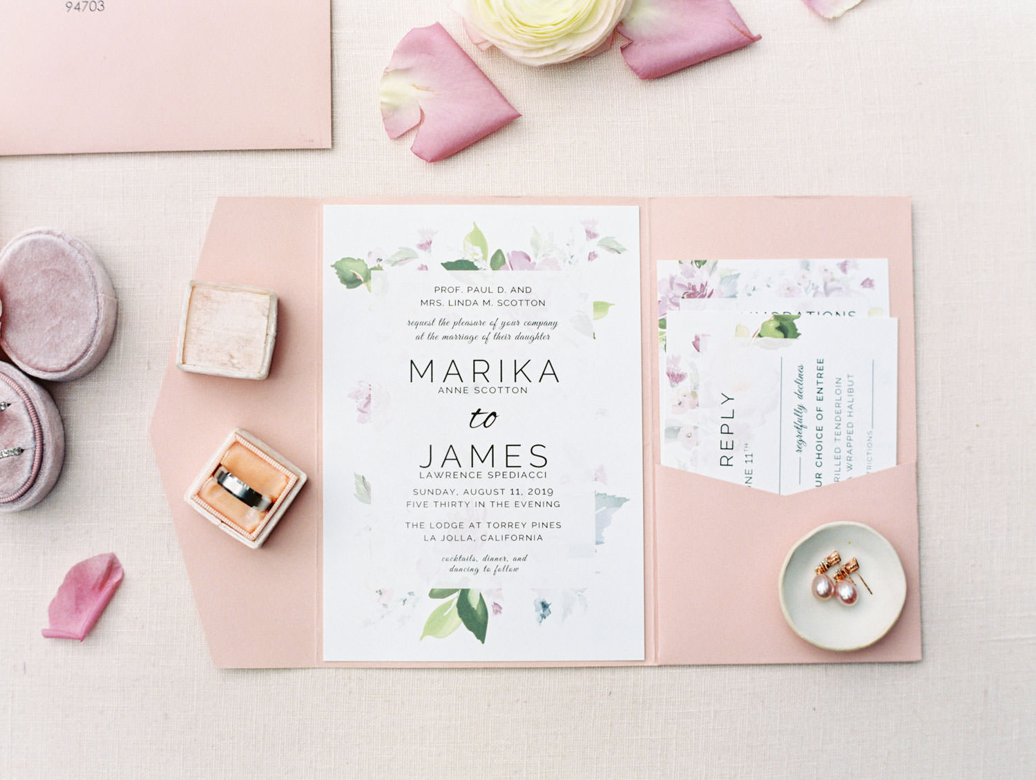 White wedding invitation with green and lavender floral border in pink envelope with pocket for detail cards, film photography by Cavin Elizabeth Photography