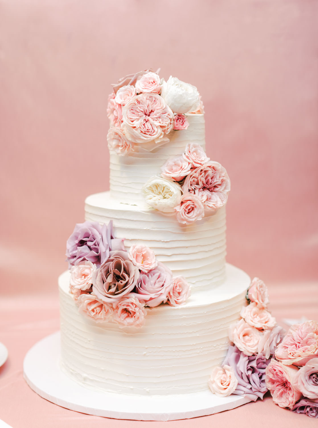 Three tier white cake topped with pink and lavender flowers, The Lodge at Torrey Pines wedding, photography by Cavin Elizabeth Photography