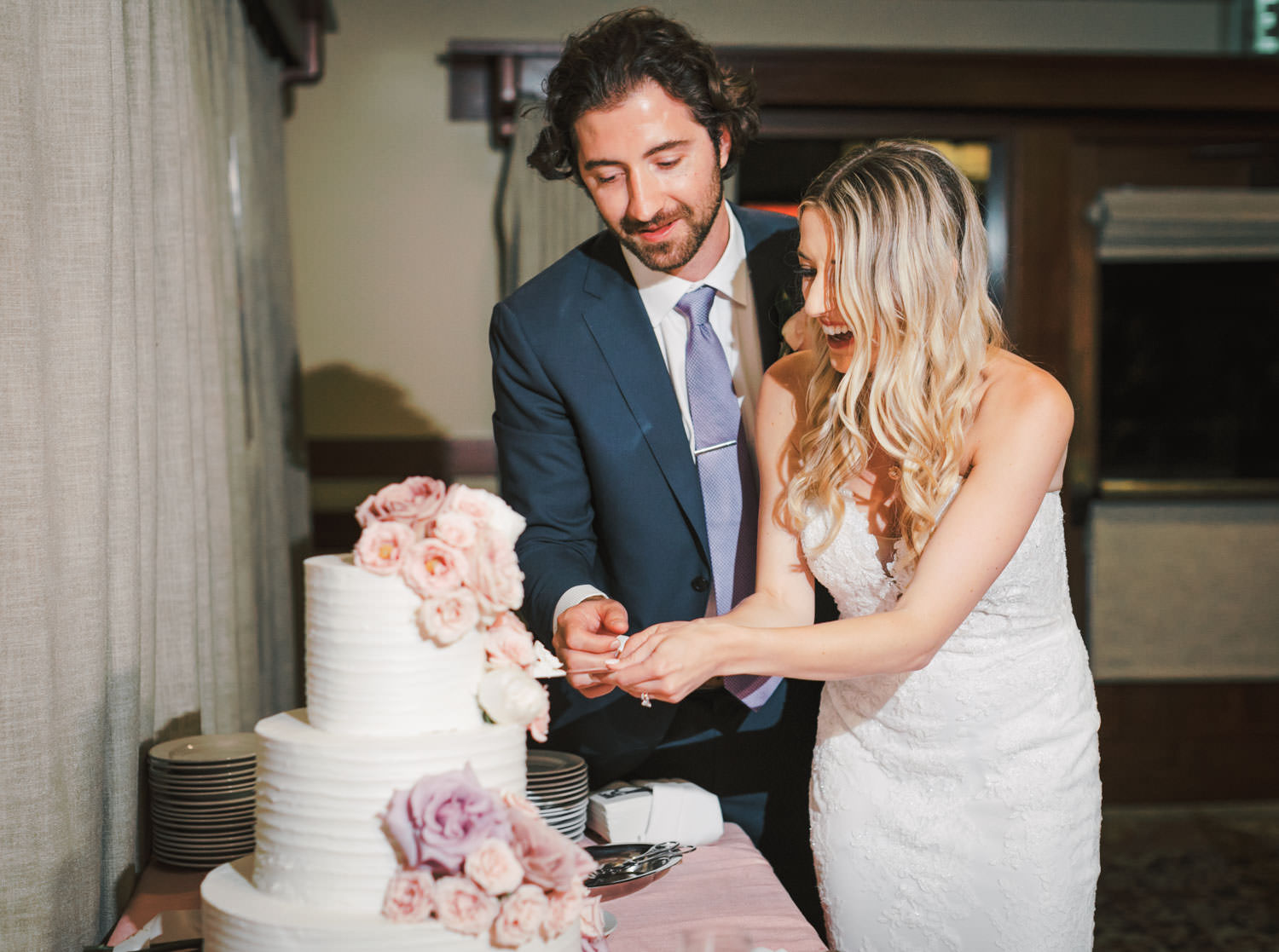 Bride and groom cut their white cake topped with pink and lavender flowers, The Lodge at Torrey Pines wedding, photography by Cavin Elizabeth Photography