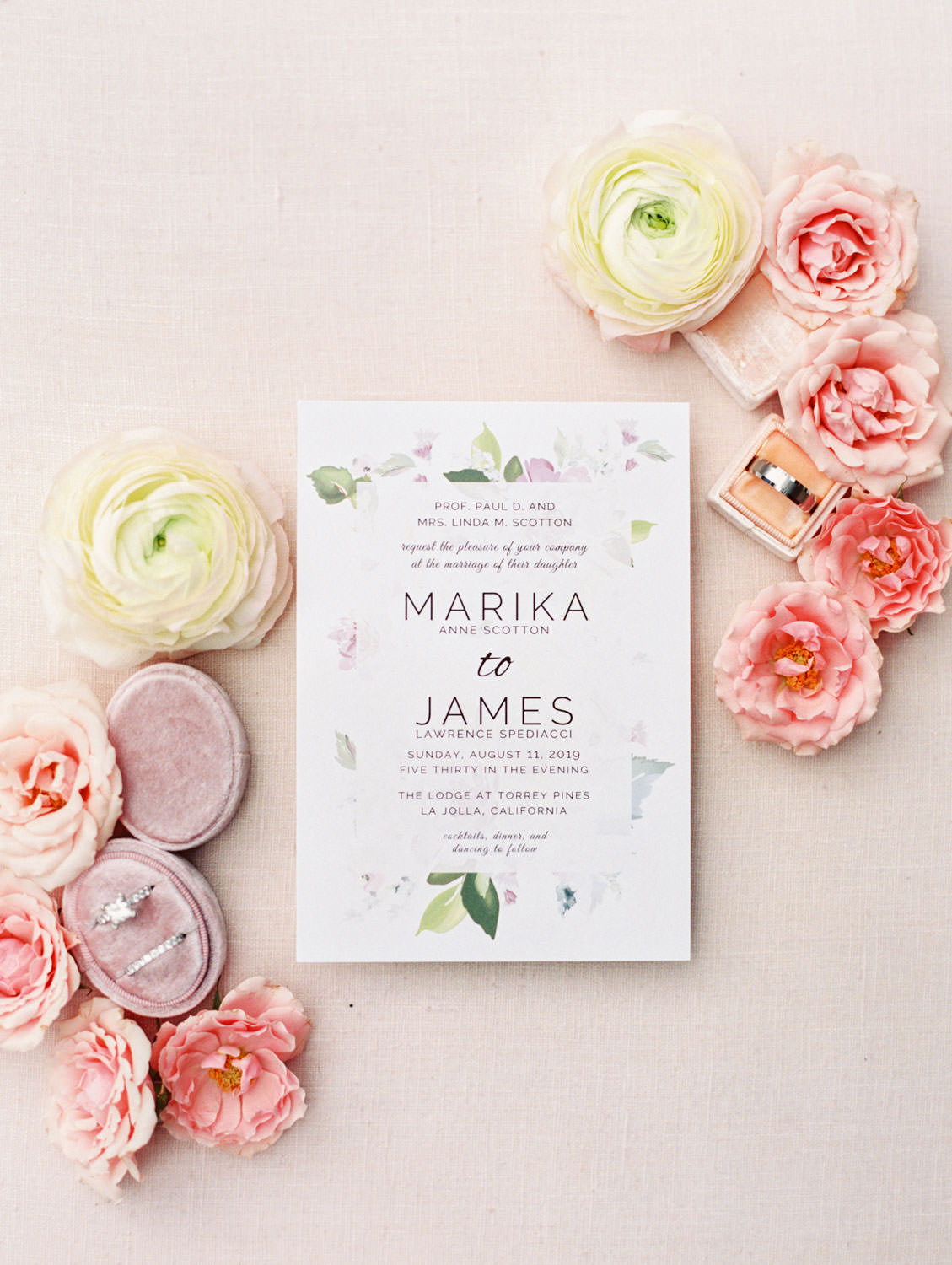 White wedding invitation with green and lavender floral border styled with wedding rings and flowers, film photography by Cavin Elizabeth Photography