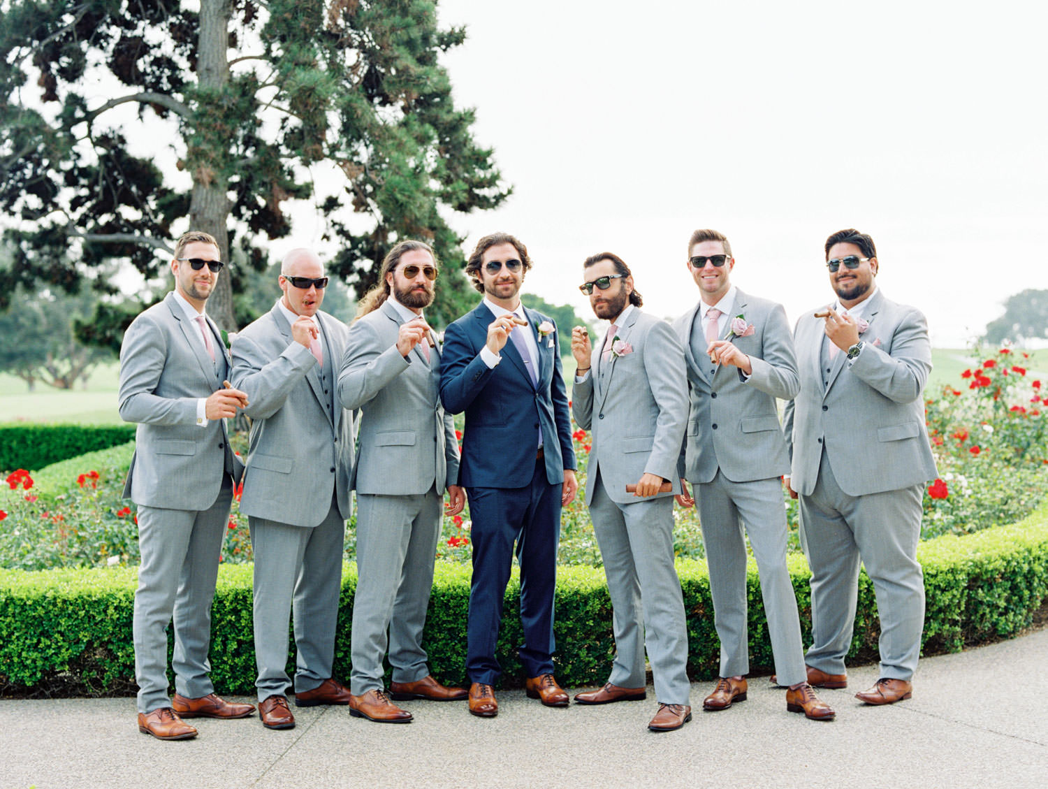 Groomsmen in light grey suits and groom in navy suit with cigars, Lodge at Torrey Pines wedding, film photography by Cavin Elizabeth Photography