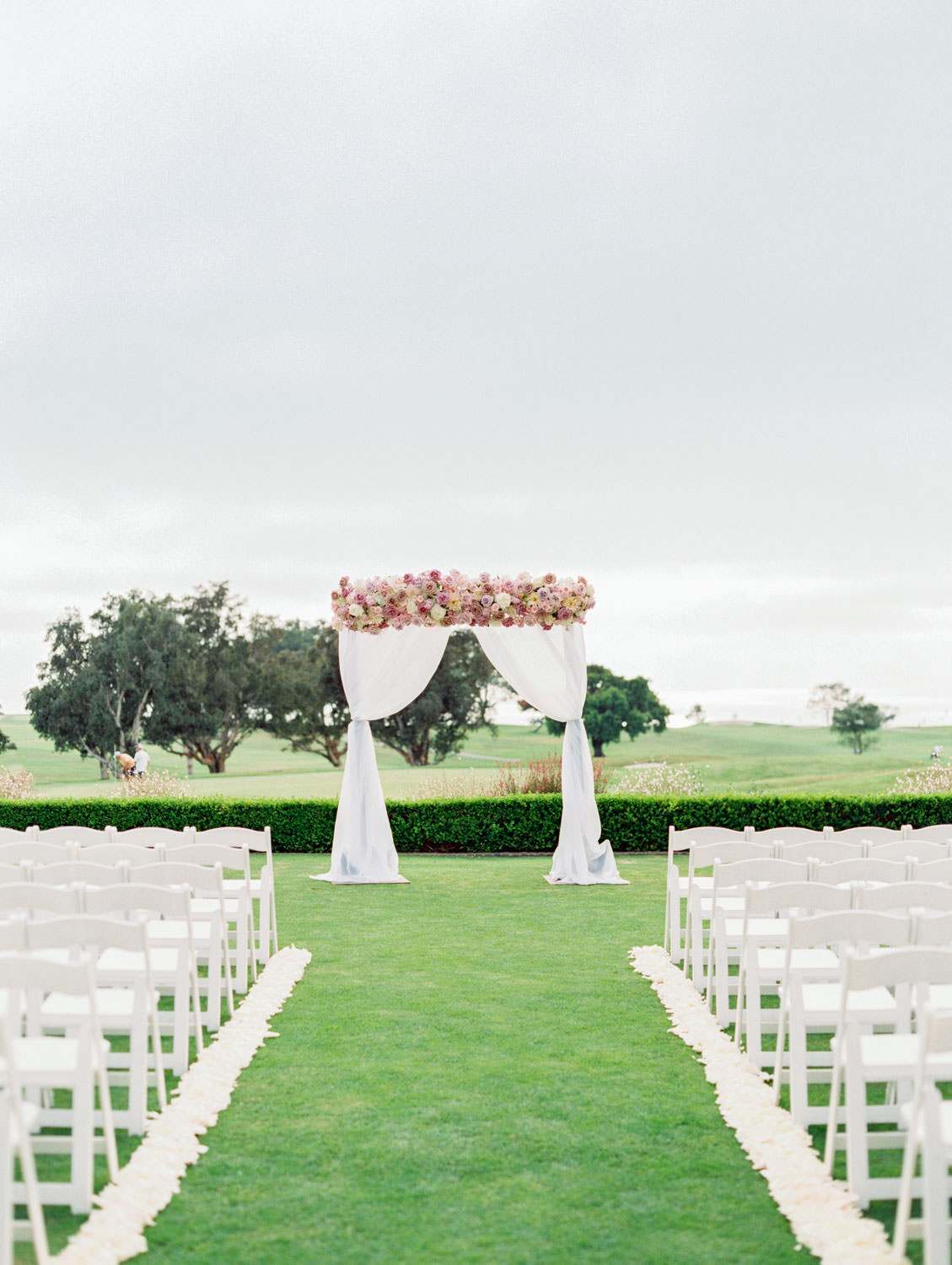 Ceremony on grassy lawn with white chairs, aisle arrangements with ivory, pink, and lavender arrangements, ceremony white draping with large arrangement of roses on top of the arch, Lodge at Torrey Pines wedding, film photography by Cavin Elizabeth Photography