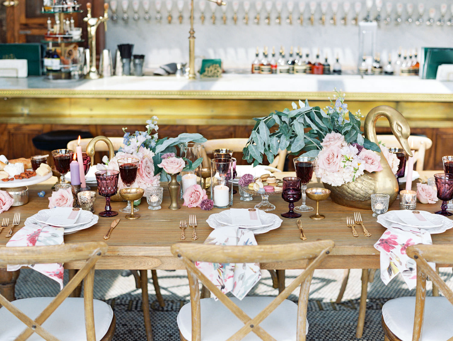 Deep purple water glass, gold coupe, crystal wine glass paired with gold flatware. Golden geese vases with ivory and blush flowers. Floral printed cotton napkins on ivory chargers with ivory menus adorned with wax seal and mauve place card. Wooden farm table with wooden crossback chairs and white cushions. Cavin Elizabeth Photography.