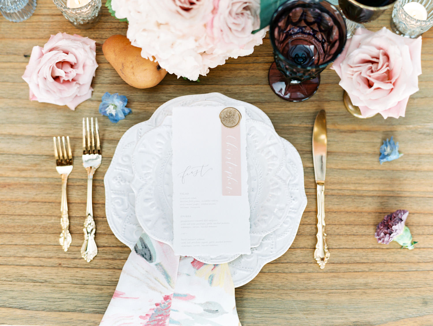 Deep purple water glass, gold coupe, crystal wine glass paired with gold flatware. Golden geese vases with ivory and blush flowers. Floral printed cotton napkins on ivory chargers with ivory menus adorned with wax seal and mauve place card. Film by Cavin Elizabeth Photography.