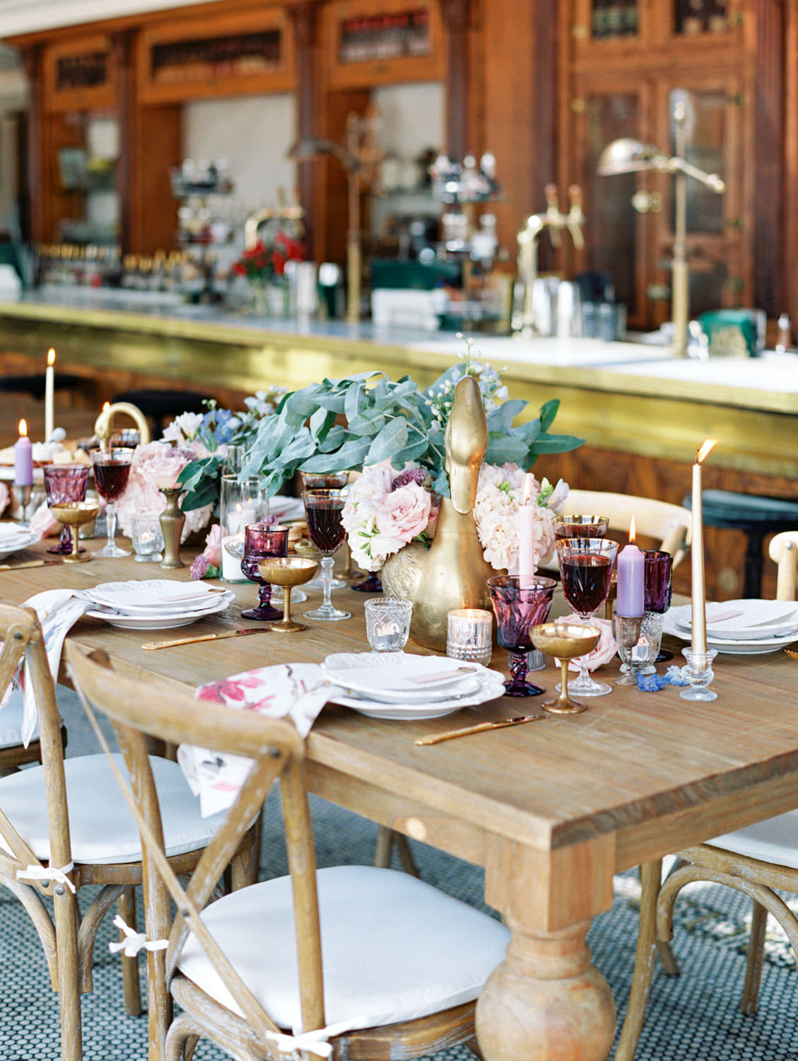 Deep purple water glass, gold coupe, crystal wine glass paired with gold flatware. Golden geese vases with ivory and blush flowers. Floral printed cotton napkins on ivory chargers with ivory menus adorned with wax seal and mauve place card. Wooden farm table with wooden crossback chairs and white cushions. Polite Provisions event. Cavin Elizabeth Photography.