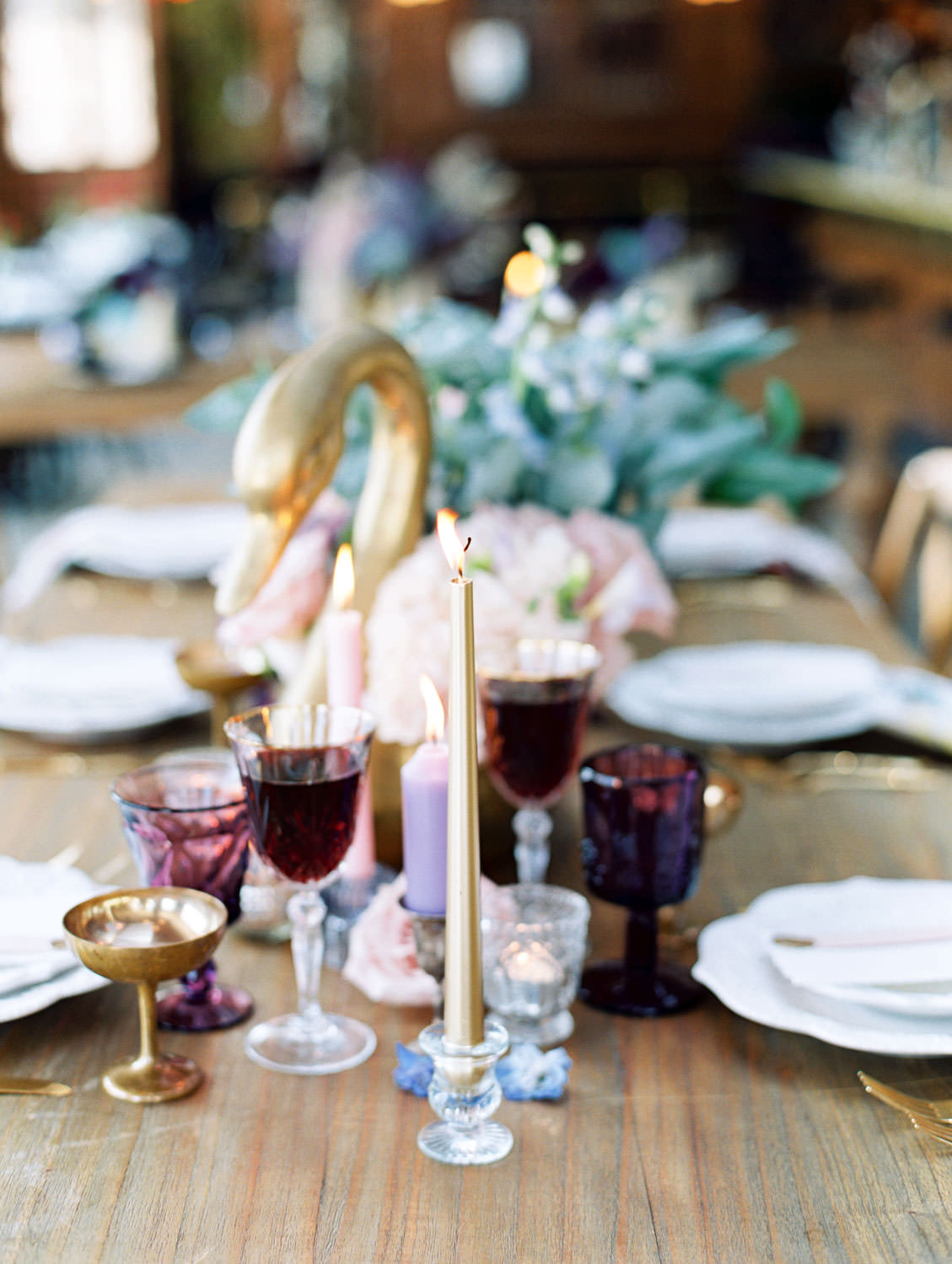 Deep purple water glass, gold coupe, crystal wine glass paired with gold flatware. Golden geese vases with ivory and blush flowers. Golden taper candle. Polite Provisions event. Cavin Elizabeth Photography.