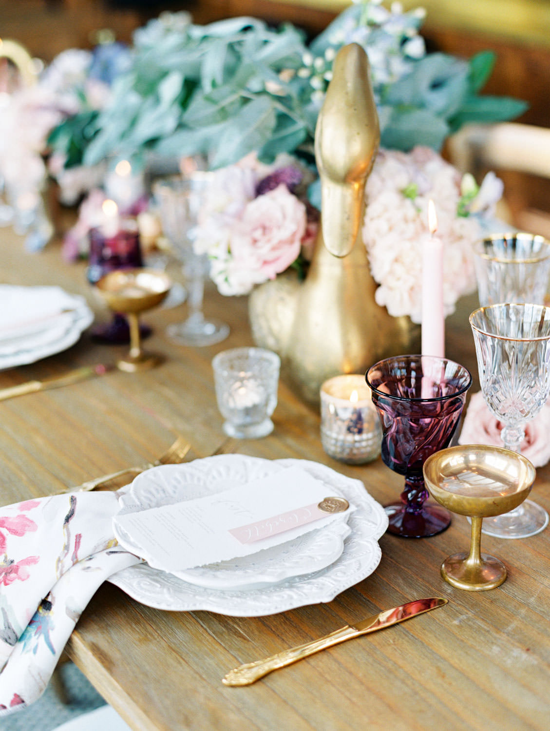 Deep purple water glass, gold coupe, crystal wine glass paired with gold flatware. Golden geese vases with ivory and blush flowers. Floral printed cotton napkins on ivory chargers with ivory menus adorned with wax seal and mauve place card. Polite Provisions event. Cavin Elizabeth Photography.