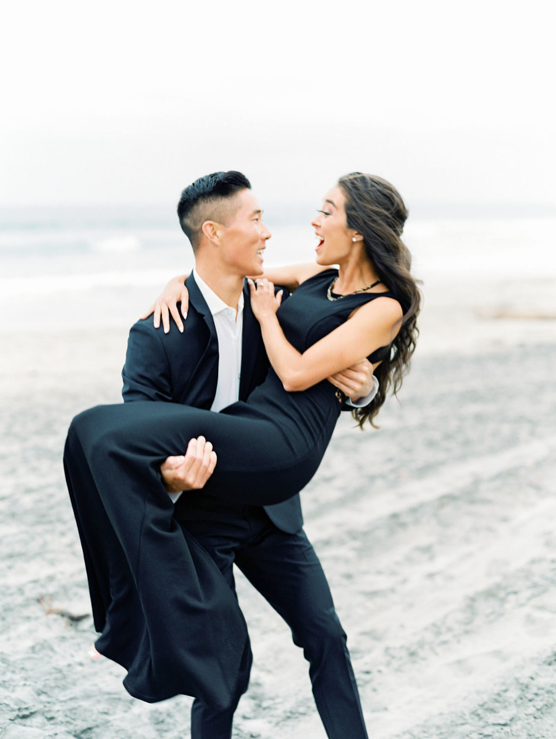 Groom holding the bride. Engagement photo outfit ideas with a formal black suit and black dress. Torrey Pines beach photos on film by Cavin Elizabeth Photography.