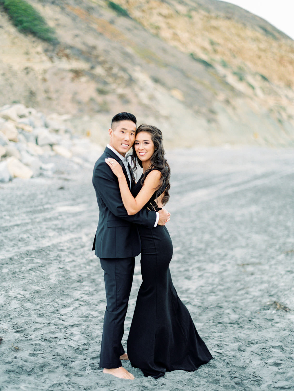 Smiling at the camera. Engagement photo outfit ideas with a formal black suit and black dress. Torrey Pines beach photos on film by Cavin Elizabeth Photography.