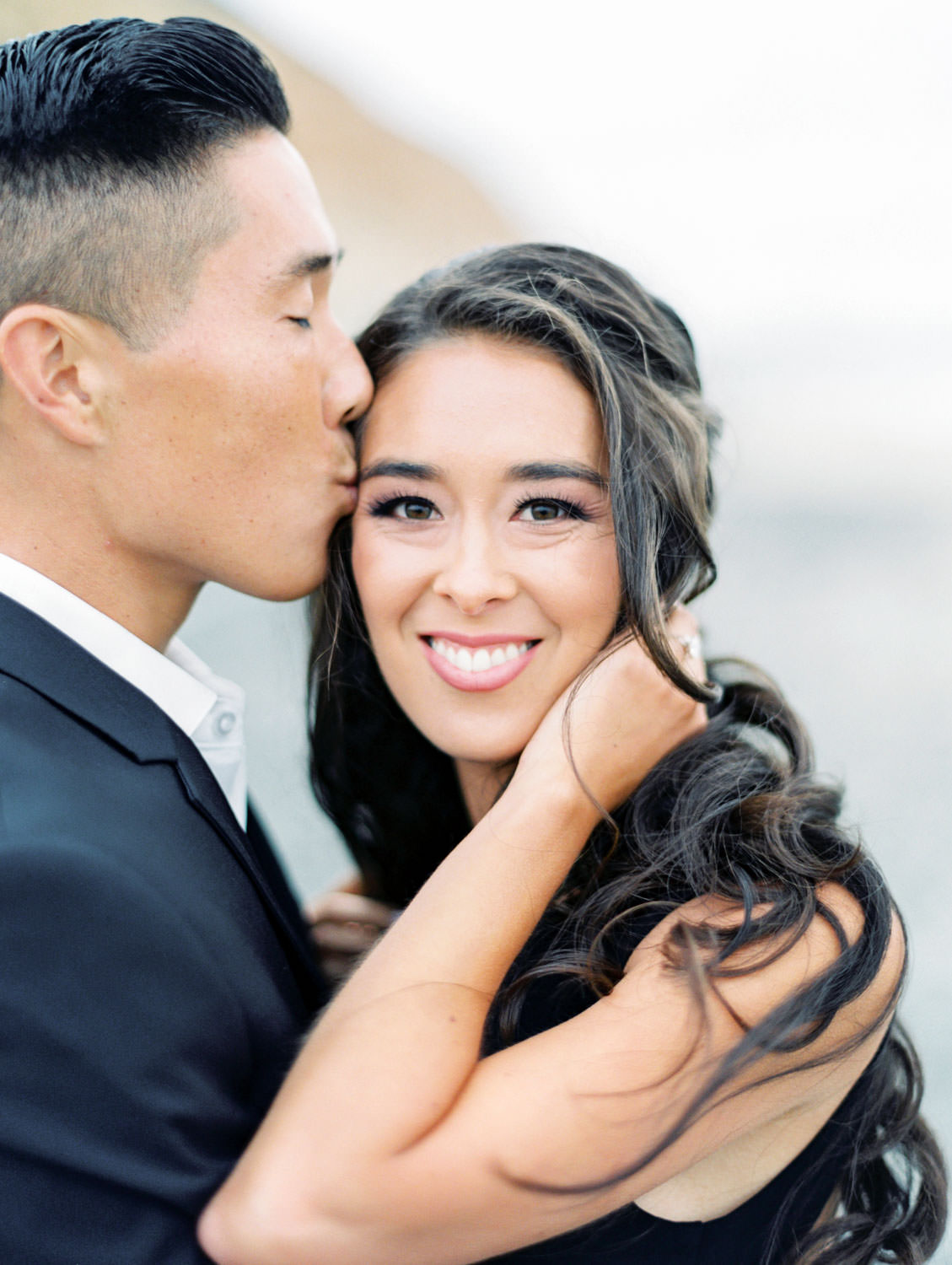 Groom kissing the bride. Engagement photo outfit ideas with a formal black suit and black dress. Bride's hair curled and down windswept. Torrey Pines beach photos on film by Cavin Elizabeth Photography.