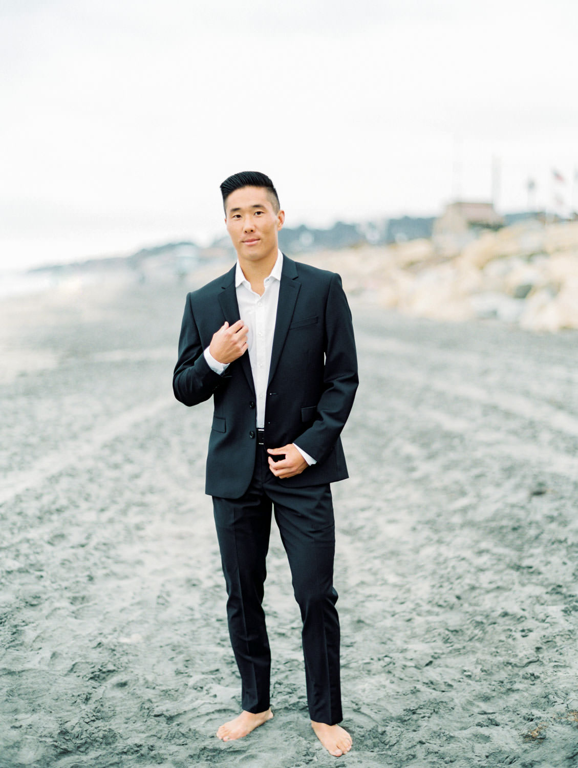 Groom in a black suit with no tie and no shoes on the beach. Torrey Pines beach photos on film by Cavin Elizabeth Photography.