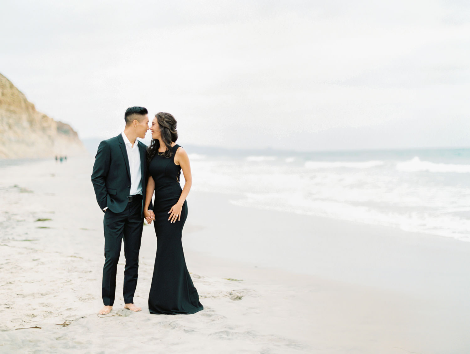 Groom rubbing noses with the bride. Engagement photo outfit ideas with a formal black suit and black dress. Torrey Pines beach photos on film by Cavin Elizabeth Photography.