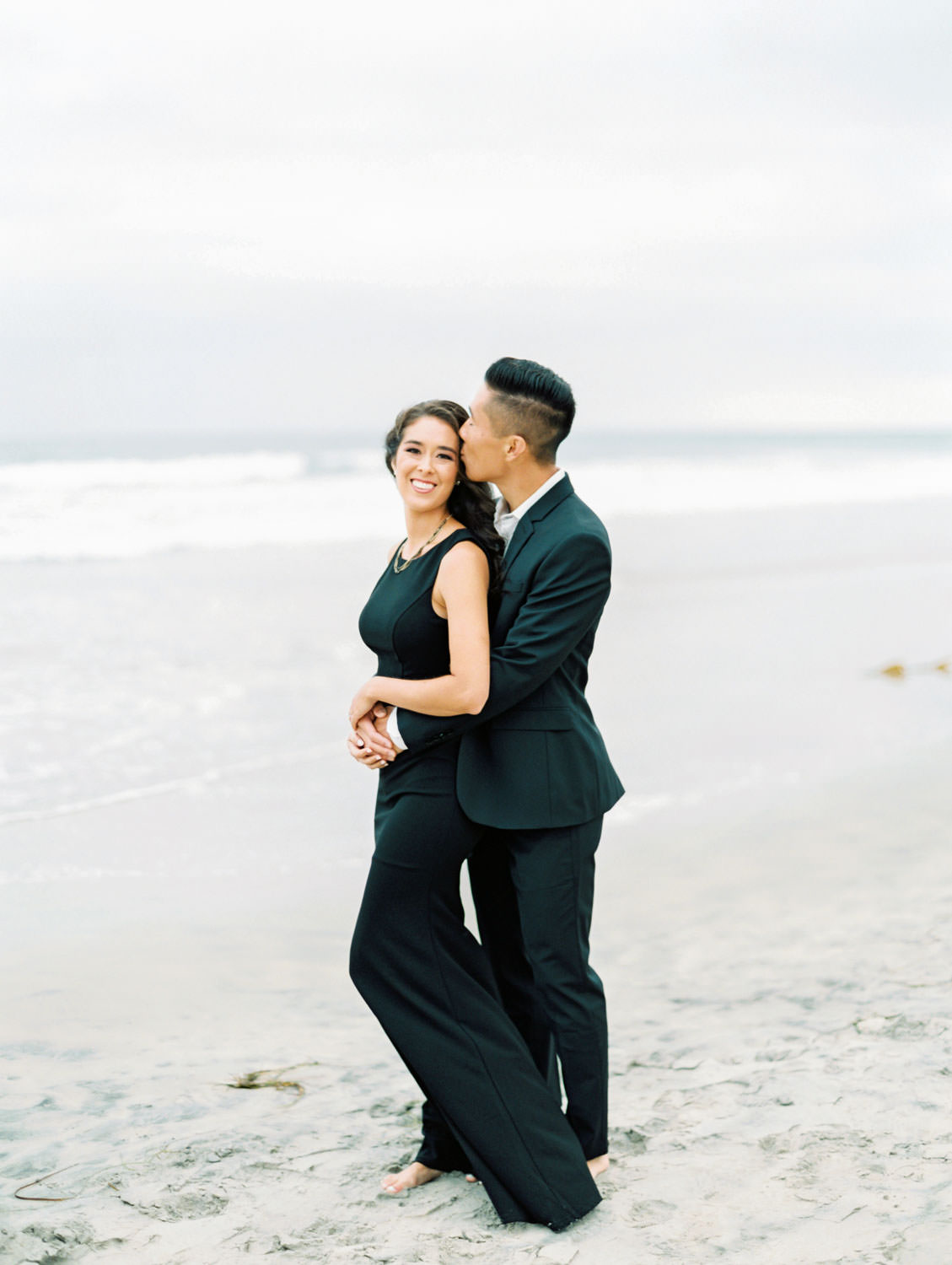 Groom kissing the bride. Engagement photo outfit ideas with a formal black suit and black dress. Torrey Pines beach photos on film by Cavin Elizabeth Photography.