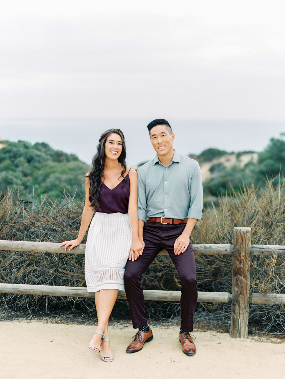 Engagement photo outfit ideas. Bride wearing a white skirt and a plum top that matches the groom's pants. Torrey Pines Engagement Photos on film by Cavin Elizabeth Photography.