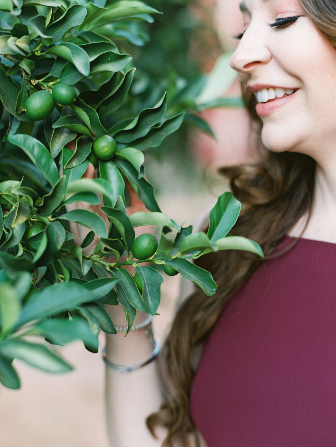 UC Riverside Engagement session in the orange grove. Bride in long berry marsala dress and groom in navy suit. Film photographer Cavin Elizabeth Photography.