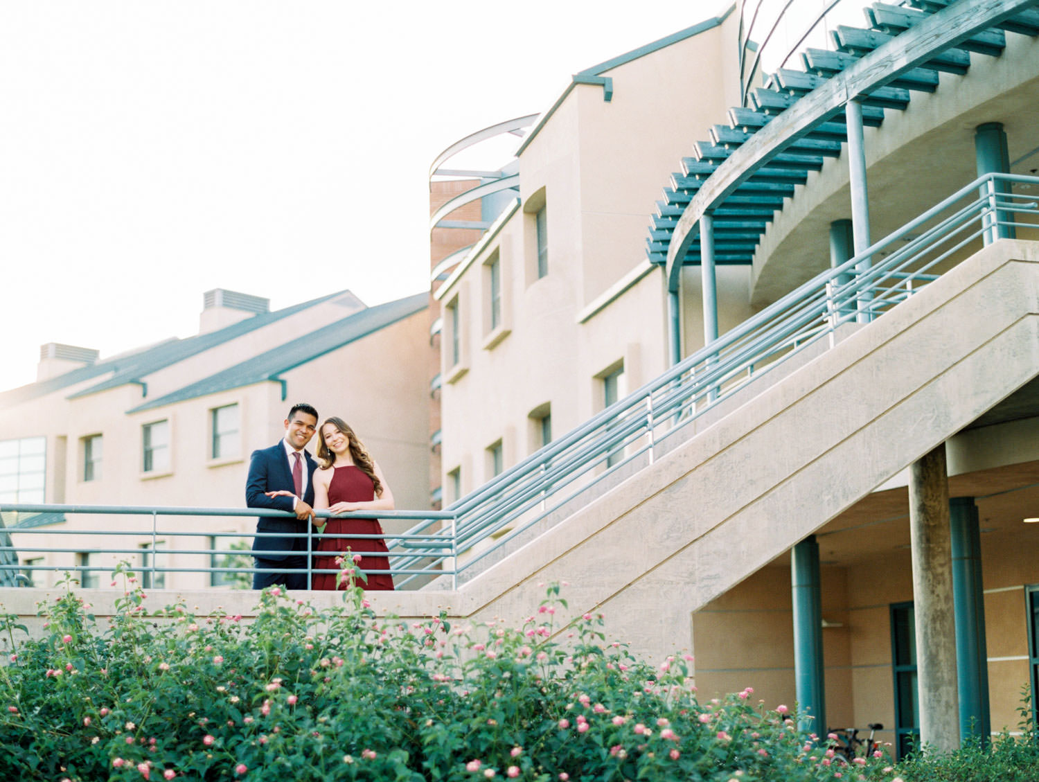 UC Riverside Engagement photos next to the dorm building where the couple met. Bride in long berry marsala dress and groom in navy suit. Film photographer Cavin Elizabeth Photography.