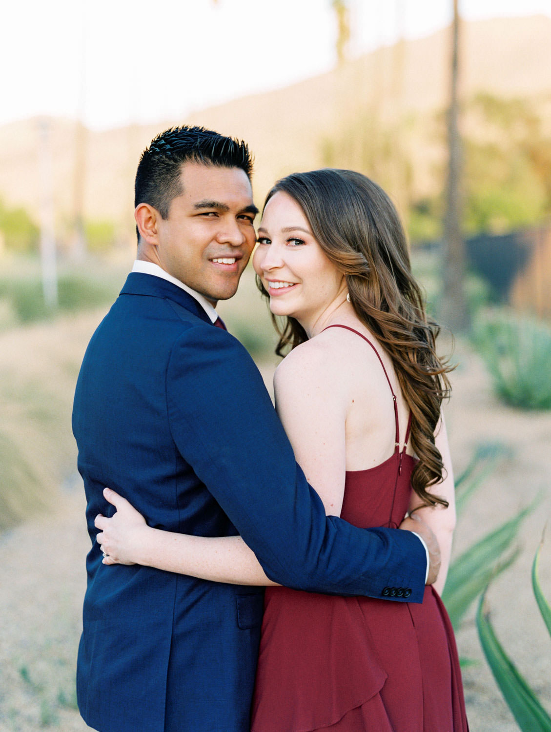 UC Riverside Engagement photos with the mountains in the background. Bride in long berry marsala dress and groom in navy suit. Film photographer Cavin Elizabeth Photography.