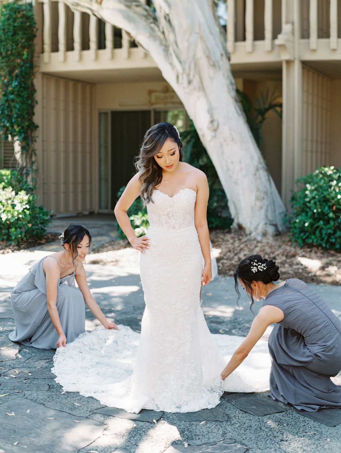 Bride's mother and sister helping her into her Martina Liana gown from The White Flower Bridal Boutique. Wedding at Rancho Bernardo Inn. Film photo by Cavin Elizabeth Photography