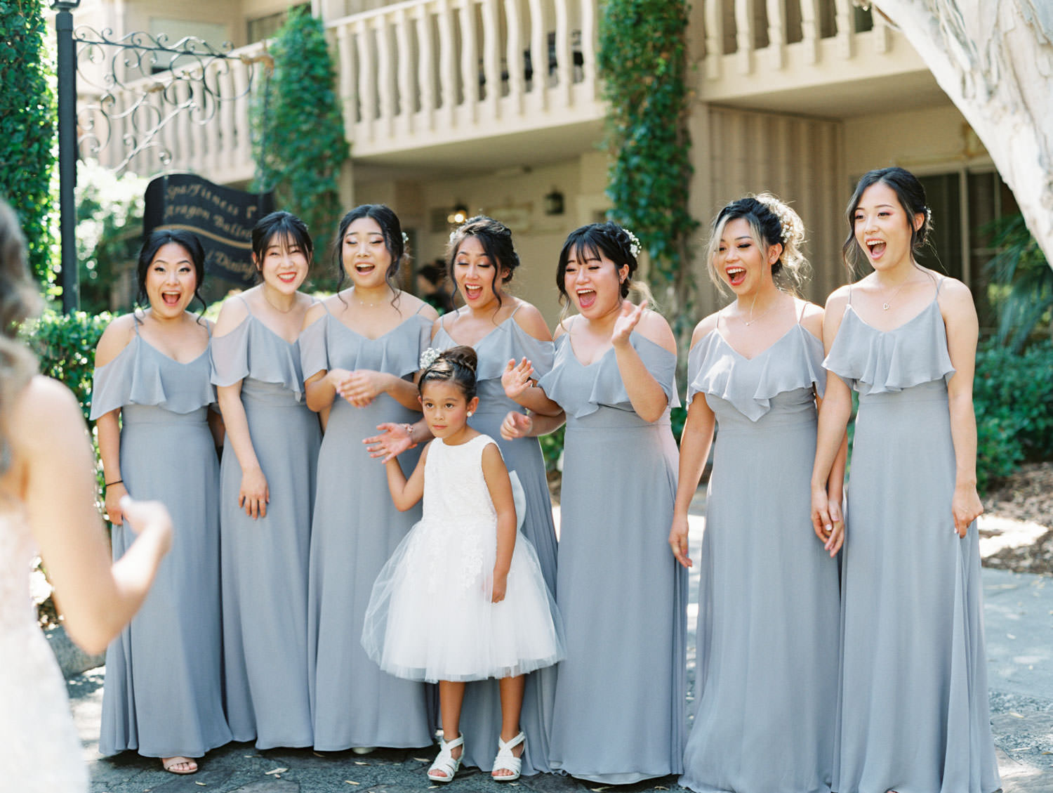 Bridesmaid first look with the bride. Bridesmaids in grey cut out sleeve gowns. Wedding at Rancho Bernardo Inn. Film photo by Cavin Elizabeth Photography