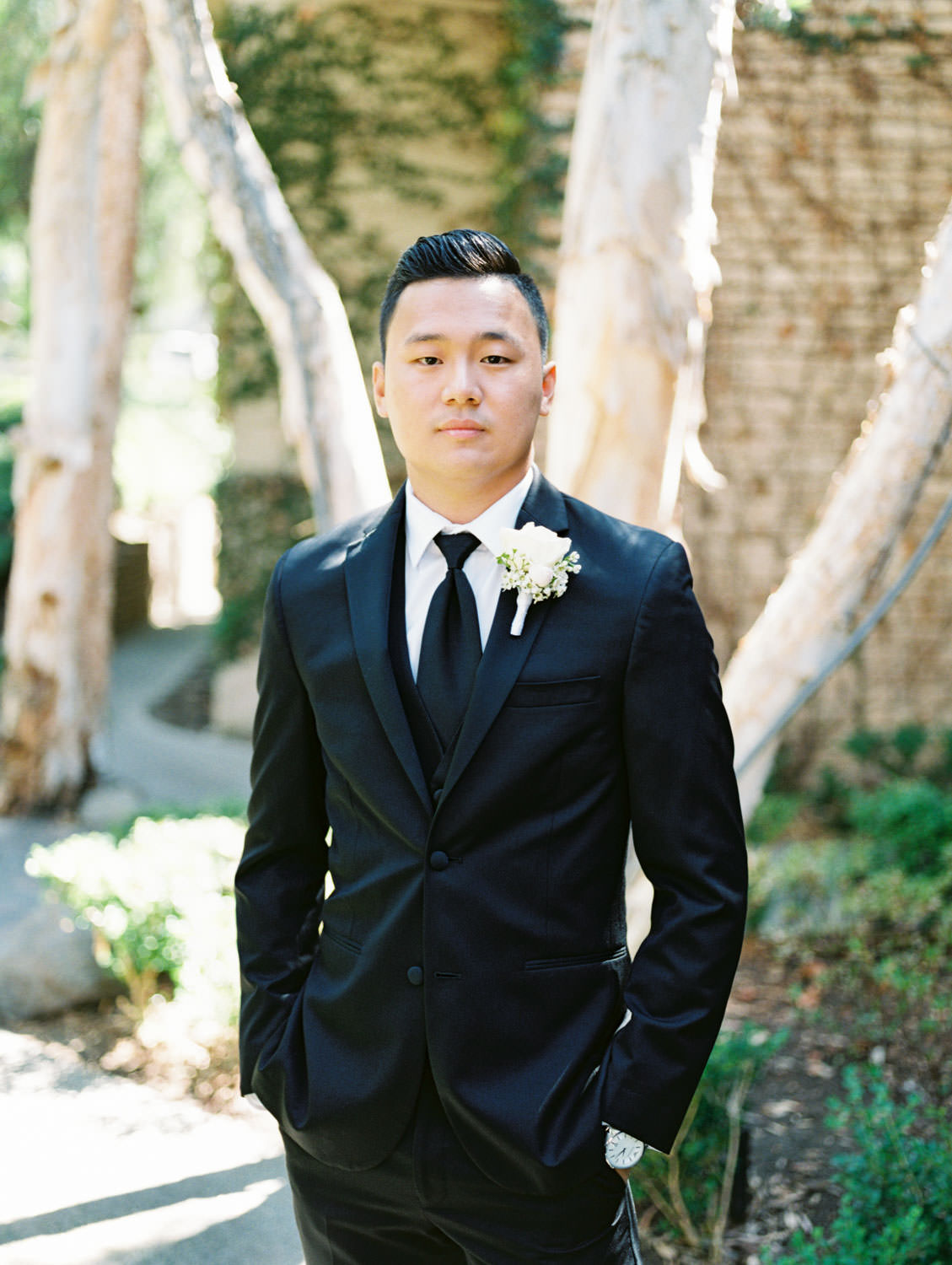 Groom in a three piece black tuxedo with white rose boutonniere. Wedding at Rancho Bernardo Inn. Film photo by Cavin Elizabeth Photography