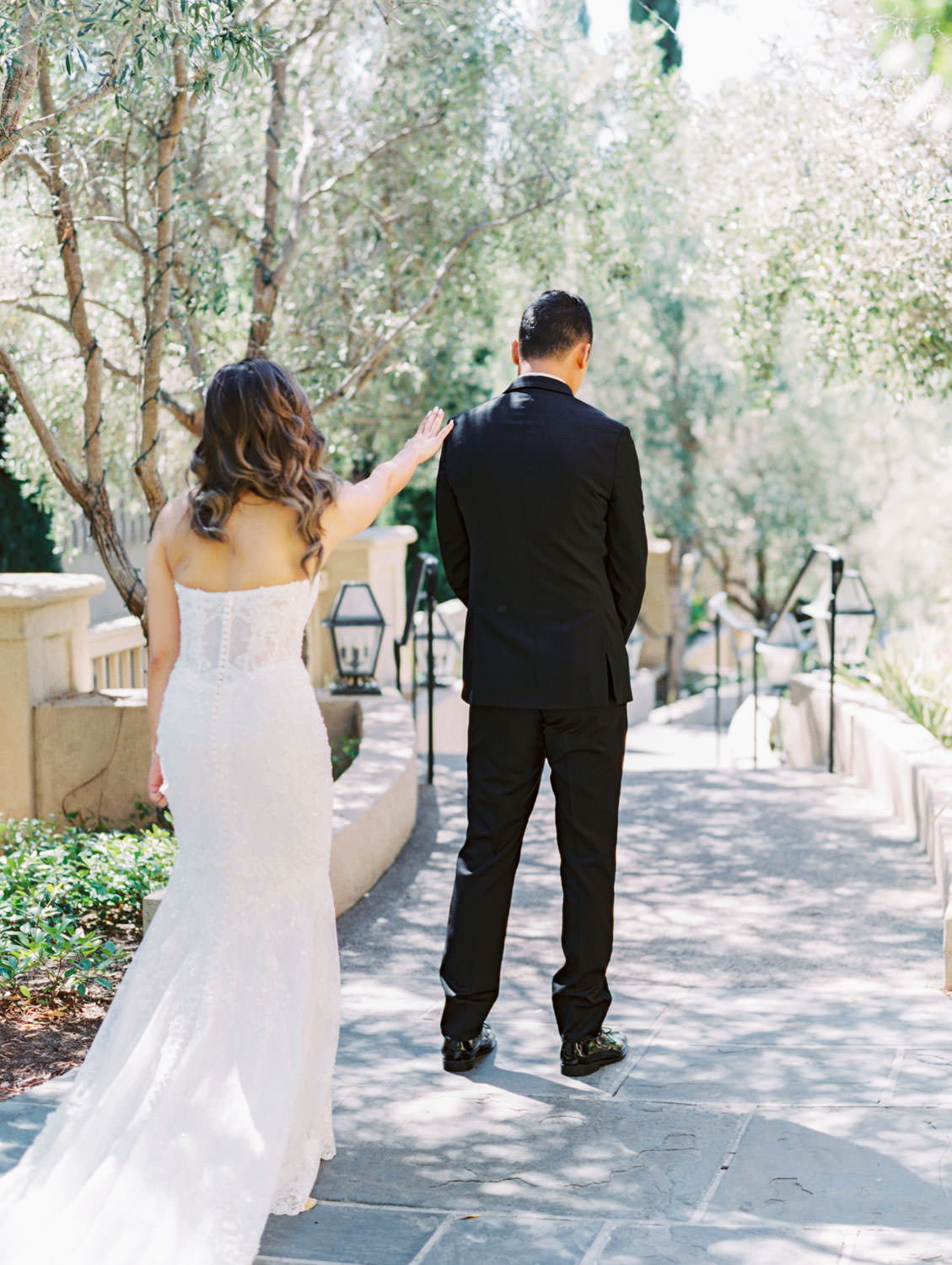 Bride and groom first look. Groom in a three piece black tuxedo and bride in a Martina Liana gown. Wedding at Rancho Bernardo Inn. Film photo by Cavin Elizabeth Photography