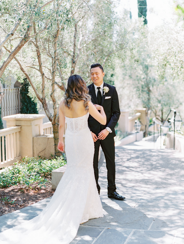 Bride and groom first look. Groom in a three piece black tuxedo and bride in a Martina Liana gown. Wedding at Rancho Bernardo Inn. Film photo by Cavin Elizabeth Photography