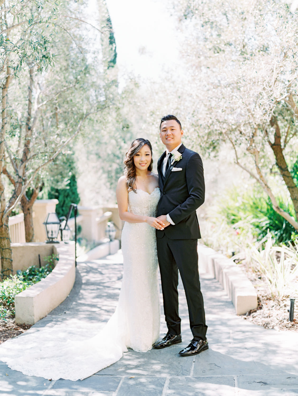 Bride and groom portrait in front of foliage. Groom in a three piece black tuxedo and bride in a Martina Liana gown. Wedding at Rancho Bernardo Inn. Film photo by Cavin Elizabeth Photography